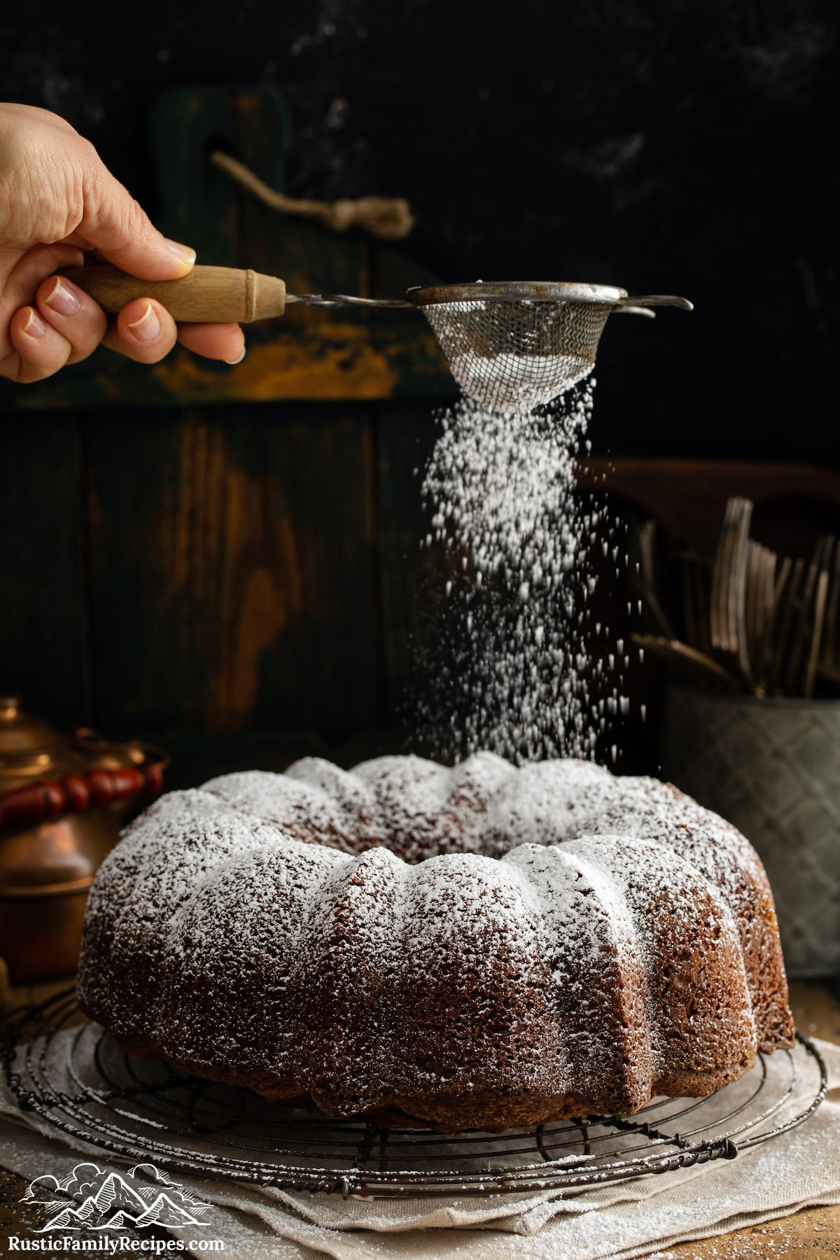 Dusting confectioners sugar on a marble cake.