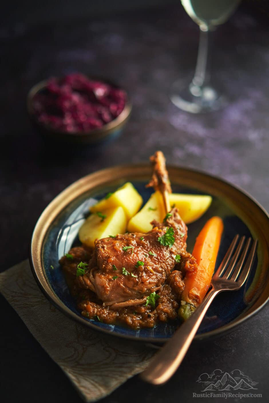 Rabbit stew on a plate with potatoes and carrots