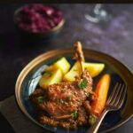 A rabbit hind leg from rabbit stew on a plate with potatoes and carrots