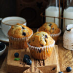 Three sourdough discard blueberry muffins on a wood board