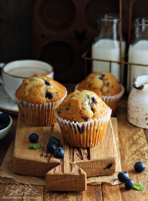 Three sourdough discard blueberry muffins on a wood board