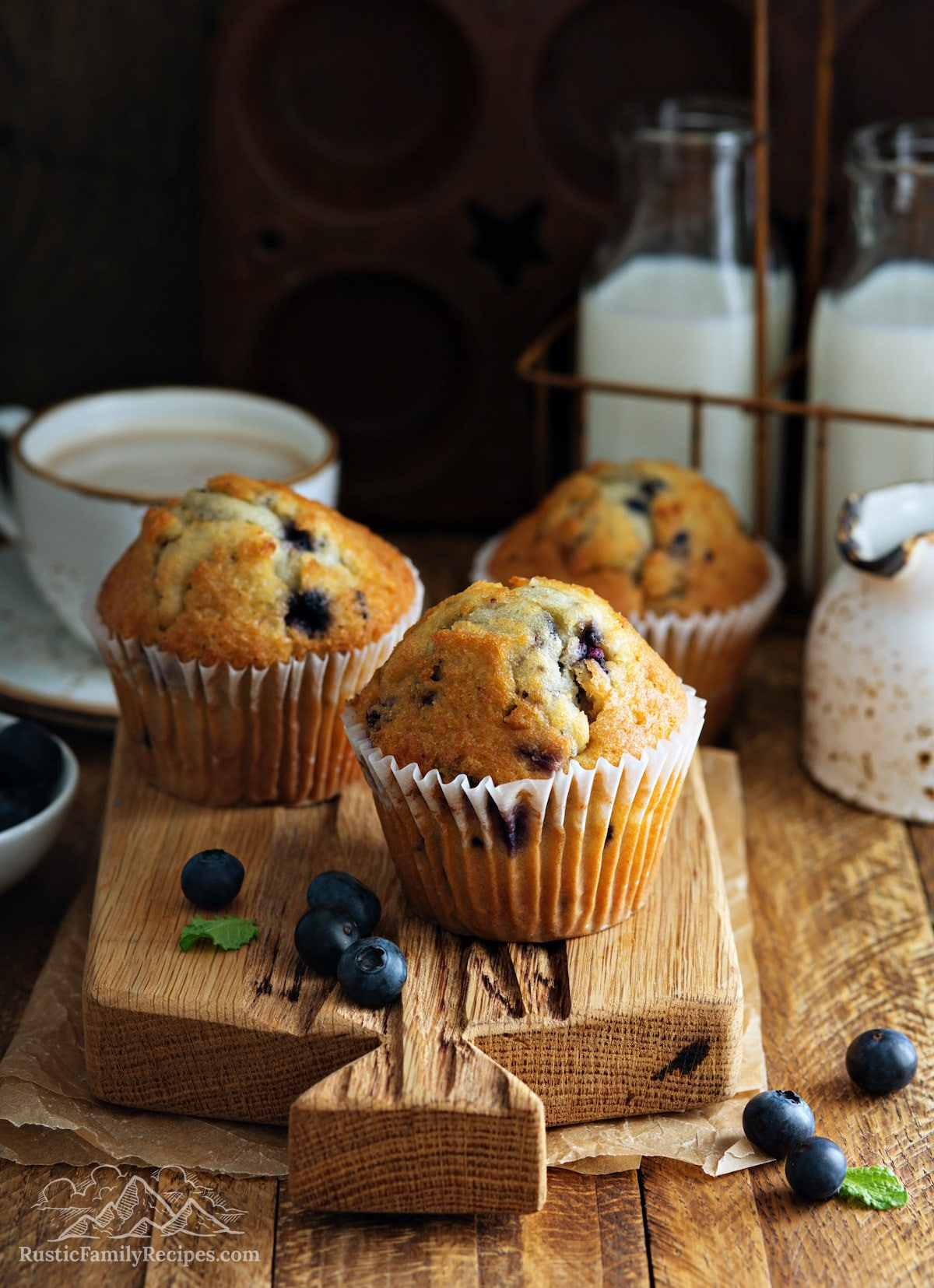 Three sourdough blueberry muffins on a wooden board with milk jugs.