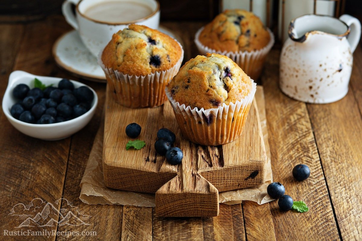 Three sourdough blueberry muffins on a wooden cutting board.