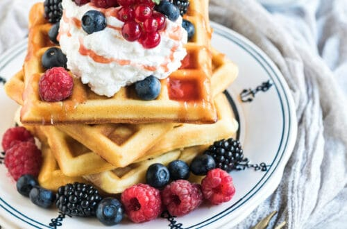 A stack of sourdough waffles topped with berries and whipped cream