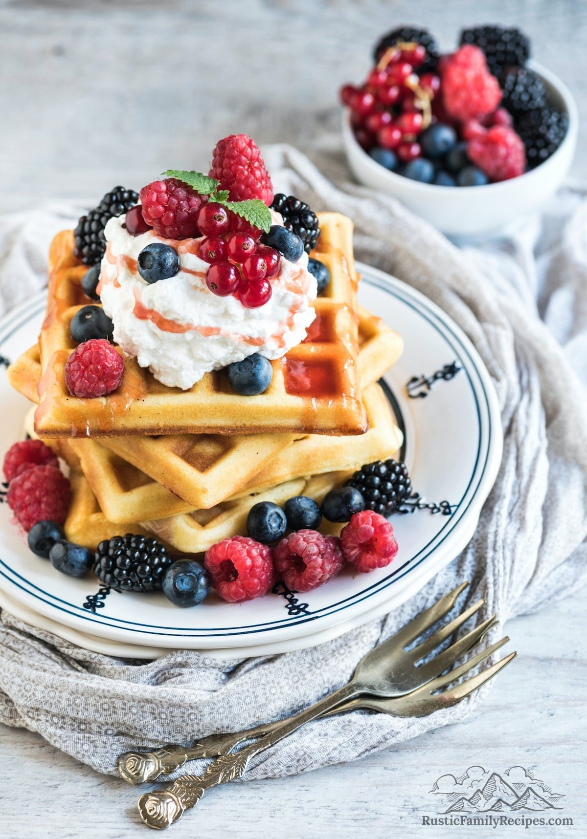 A plate with 3 sourdough waffles topped with berries and cream