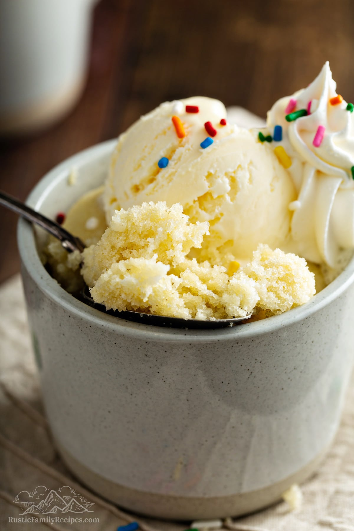 A spoon scooping out moist vanilla cake in a mug with ice cream.