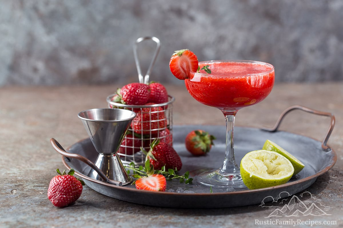 A frozen strawberry margarita with lime wedges and strawberries