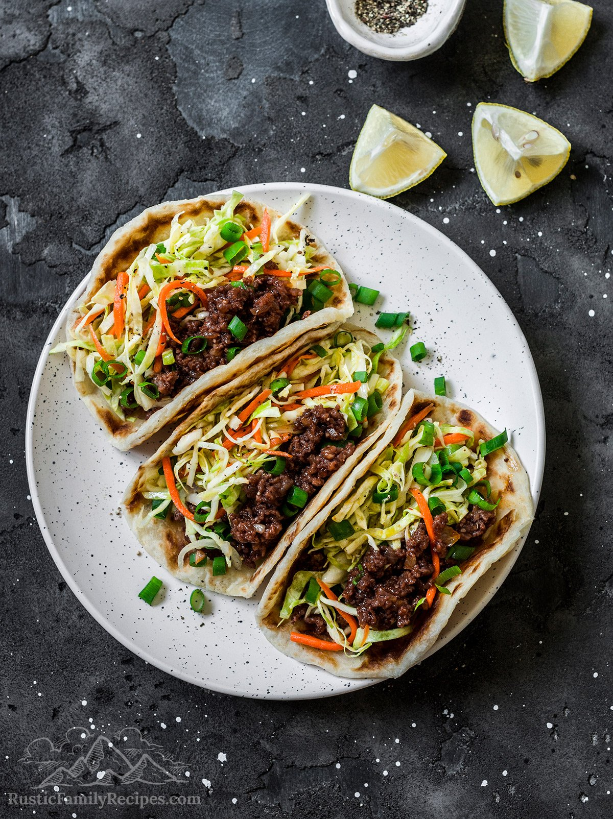 A white plate with three ground beef tacos