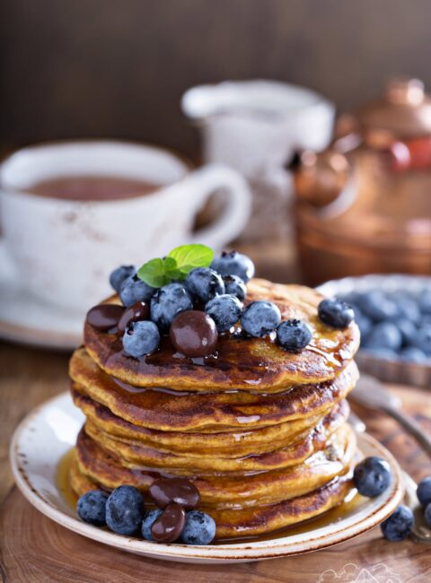 A stack of pumpkin pancakes topped with blueberries and chocolate raisins.