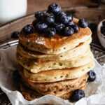 A stack of sourdough pancakes topped with blueberries