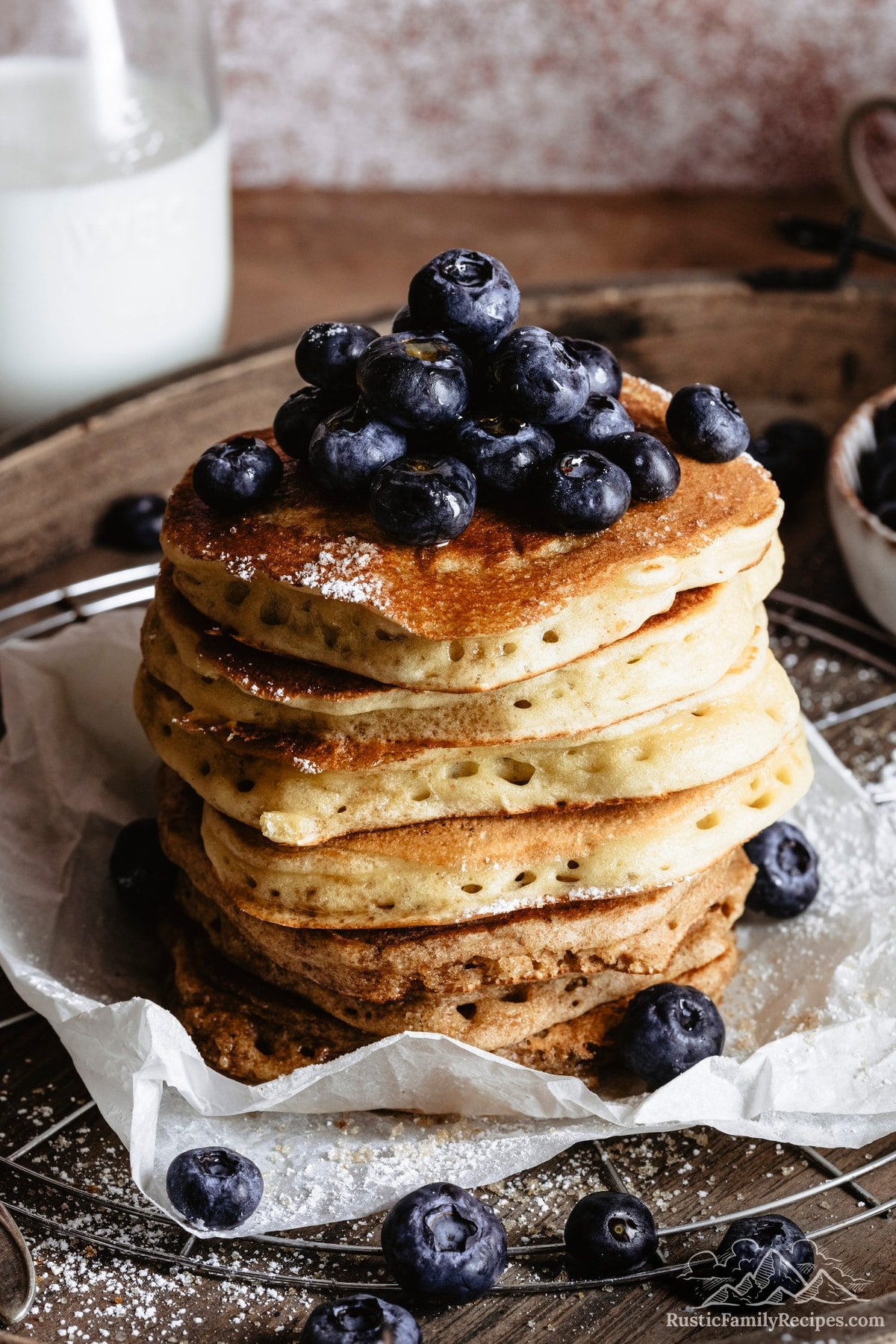 A stack of fluffy sourdough pancakes topped with blueberries.