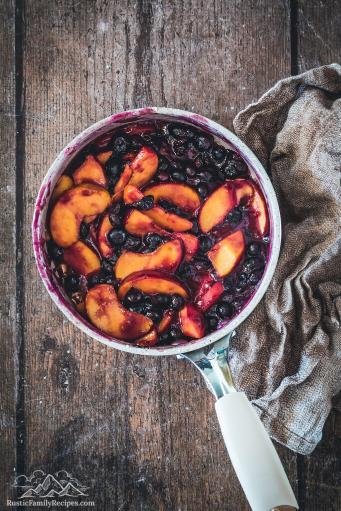 Cooked blueberry peach cobbler filling in a pot