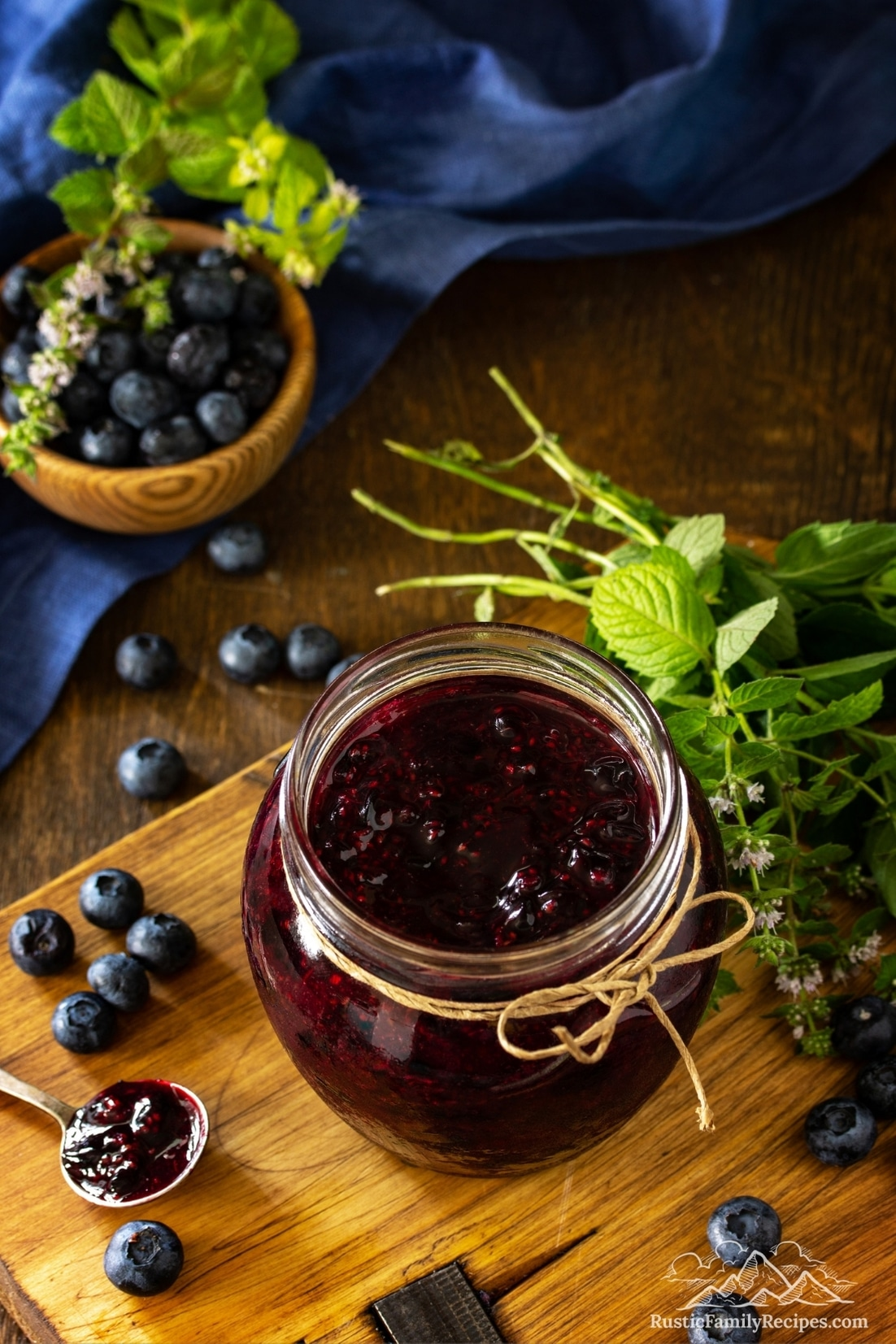 A jar on a wooden table with homemade blueberry sauce