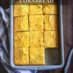 Easy Cheddar Cornbread in a baking dish cut into 12 squares with one piece missing.
