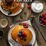 Plates with stacks of pancakes topped with berries