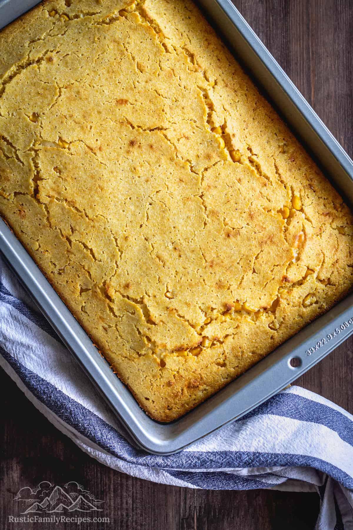 Lightly golden baked Easy Cheddar Cornbread in a baking pan.