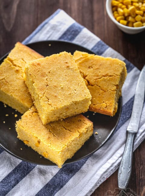 Four pieces of Easy Cheddar Cornbread on a plate on top of a napkin with a knife.