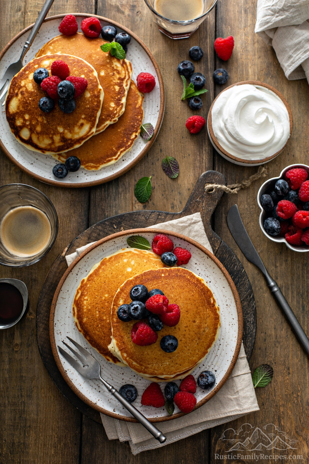 Aerial view of two plates of fluffy pancake stacks topped with berries