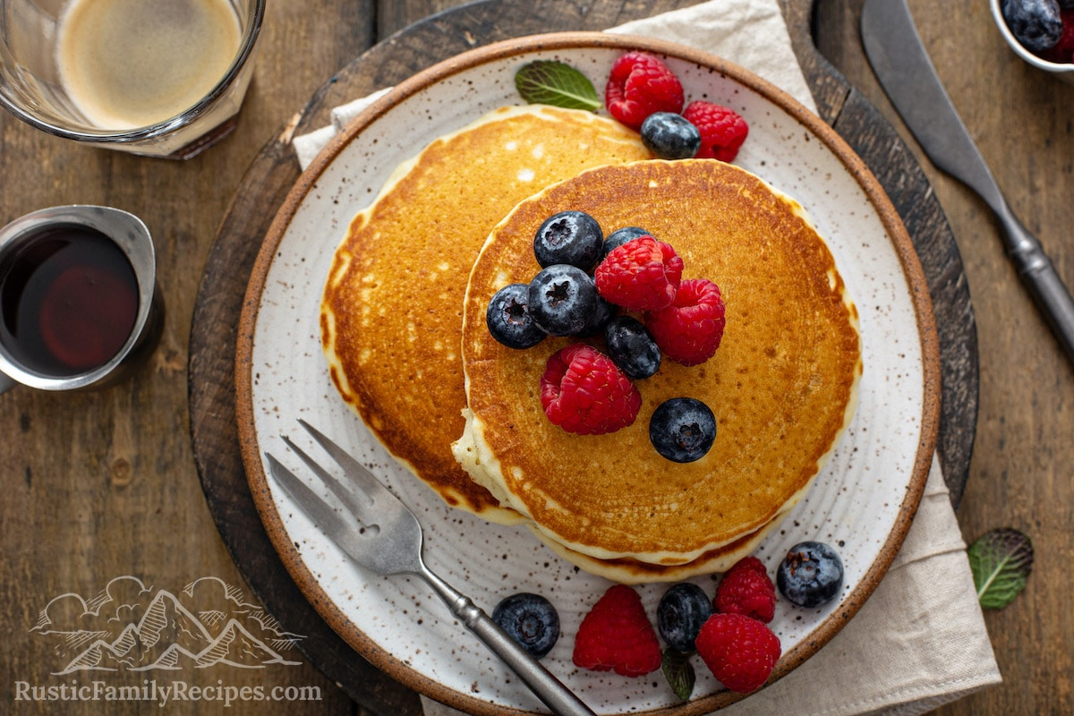 A plate of old fashioned pancakes topped with fresh berries