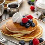 3 pancakes stacked topped with fresh berries and whipped cream