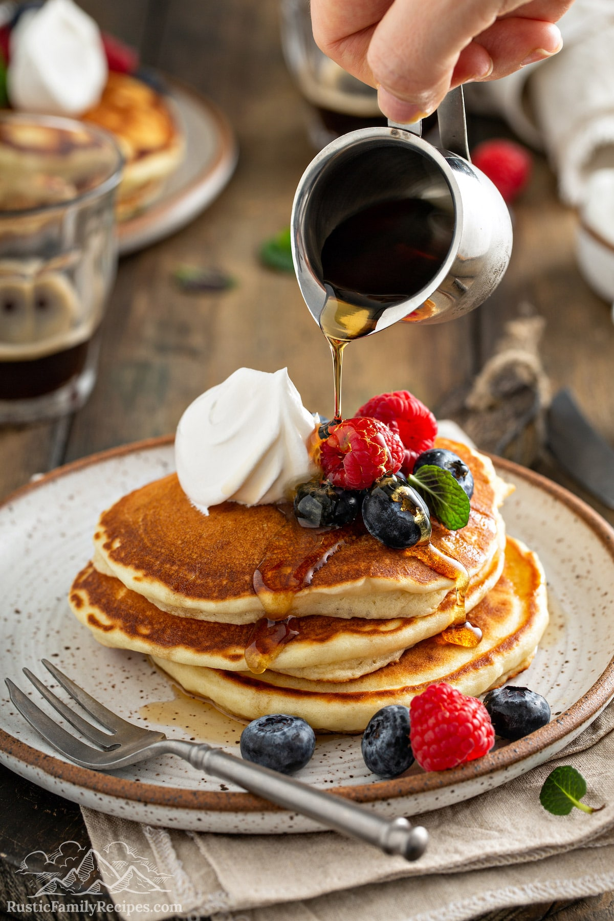 Maple syrup being poured over a stack of fluffy pancakes