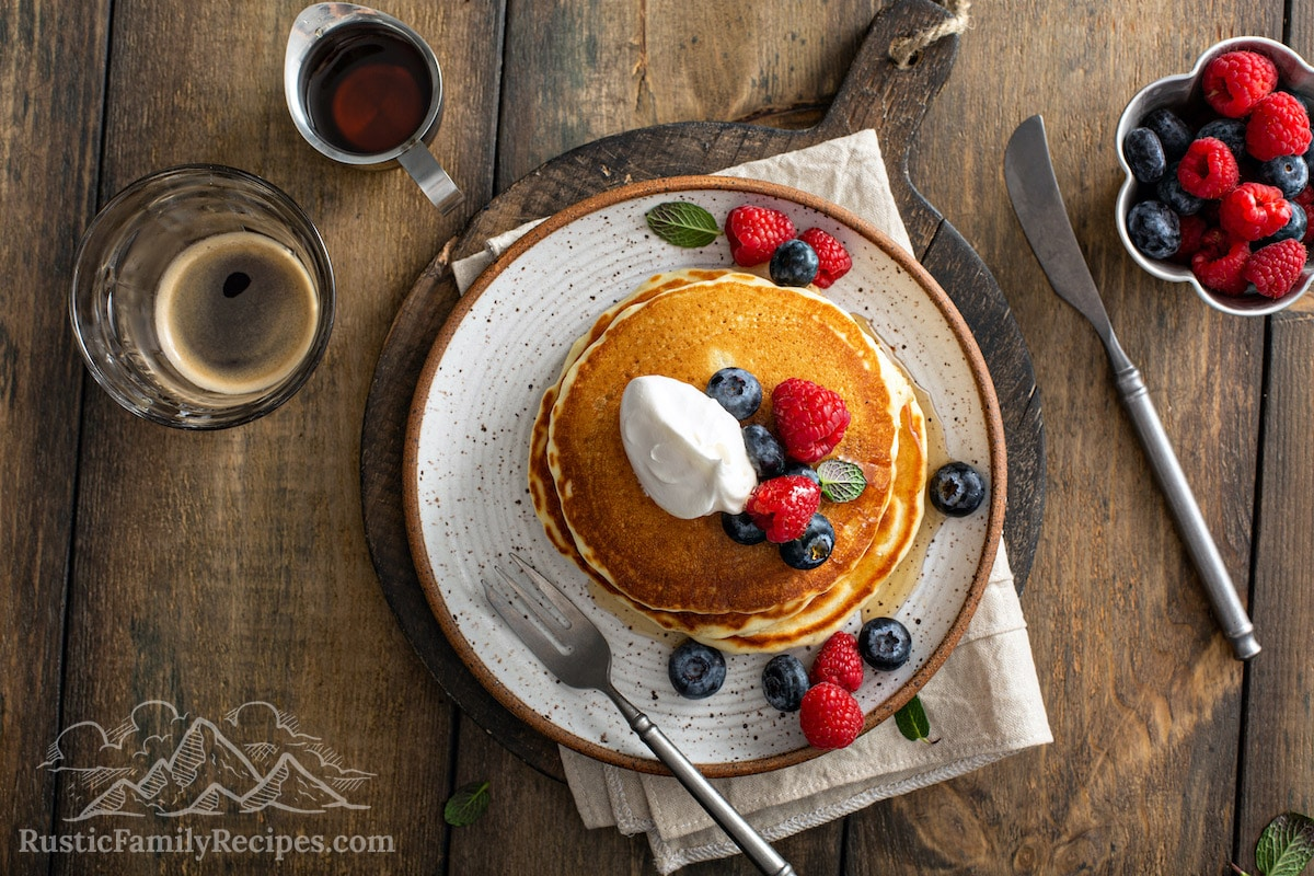 Aerial view of a stack of old fashioned pancakes topped with berries and whipped cream