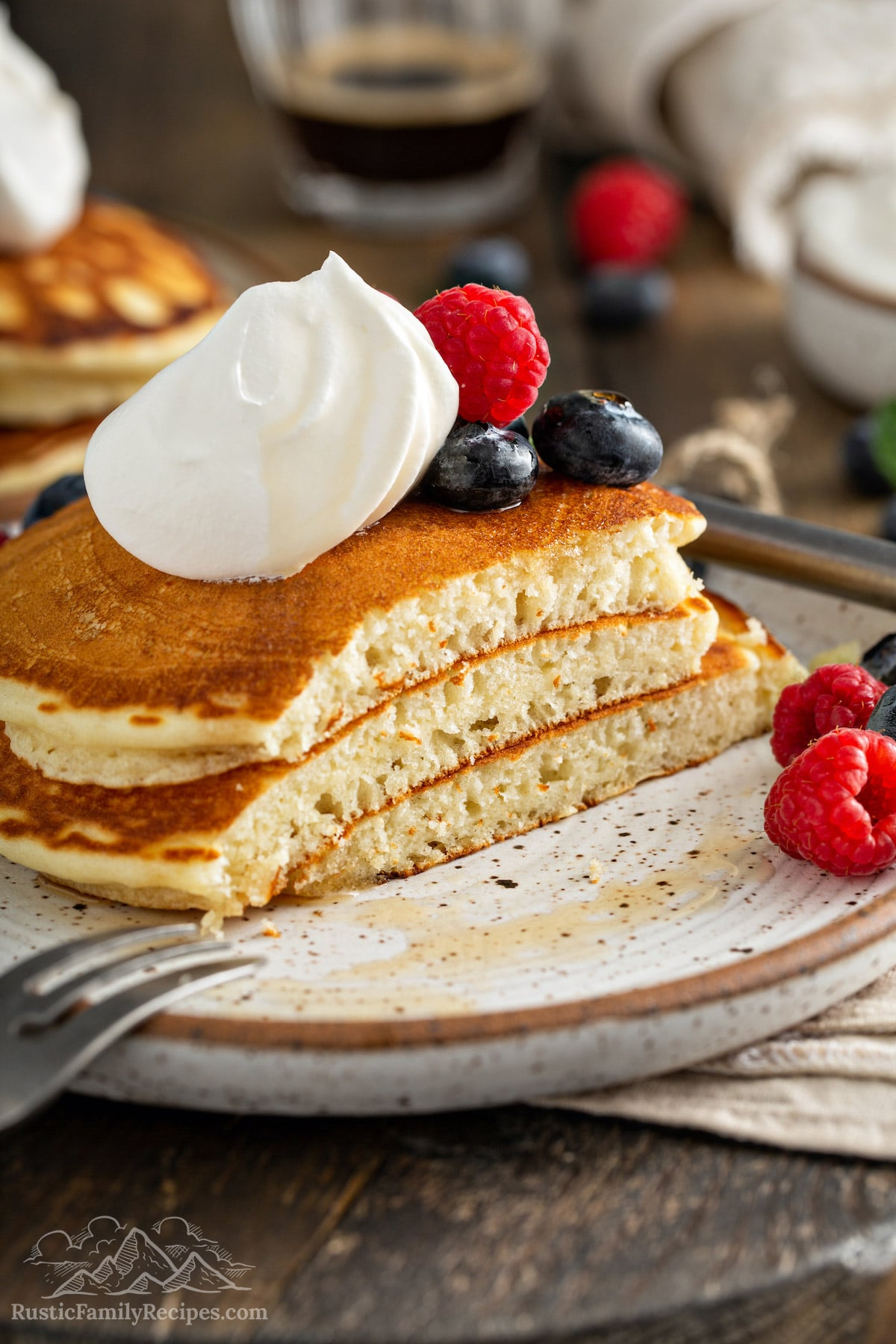 A stack of fluffy pancakes on a plate with a bite sliced off