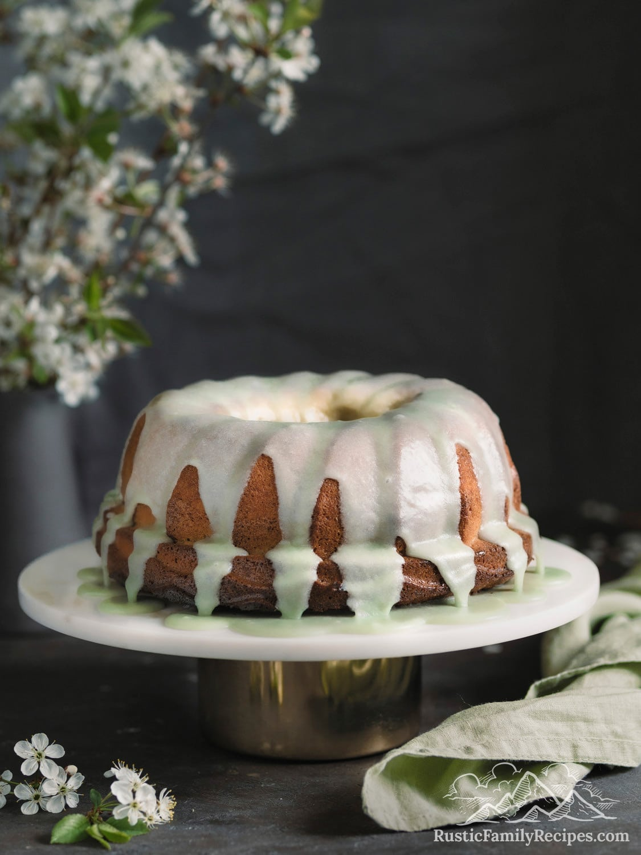 A lemon bundt cake with matcha glaze on a cake stand