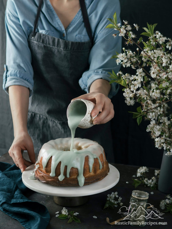 Woman pouring matcha glaze on a lemon bundt cake