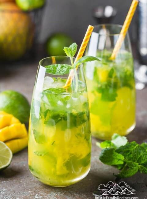 Two mango mojitos in tall glasses with orange straws