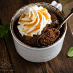 A nutella mug cake with a scoop taken out topped by whipped cream