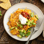A plate of sweet potato migas topped with sour cream, salsa and avocado