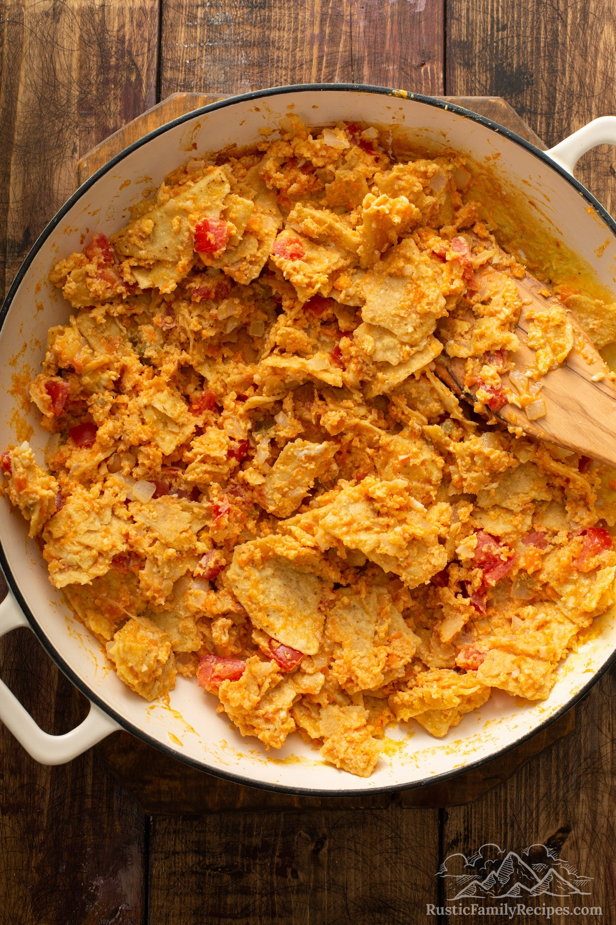 Eggs, sweet potatoes and tortilla chips being scrambled into a pan