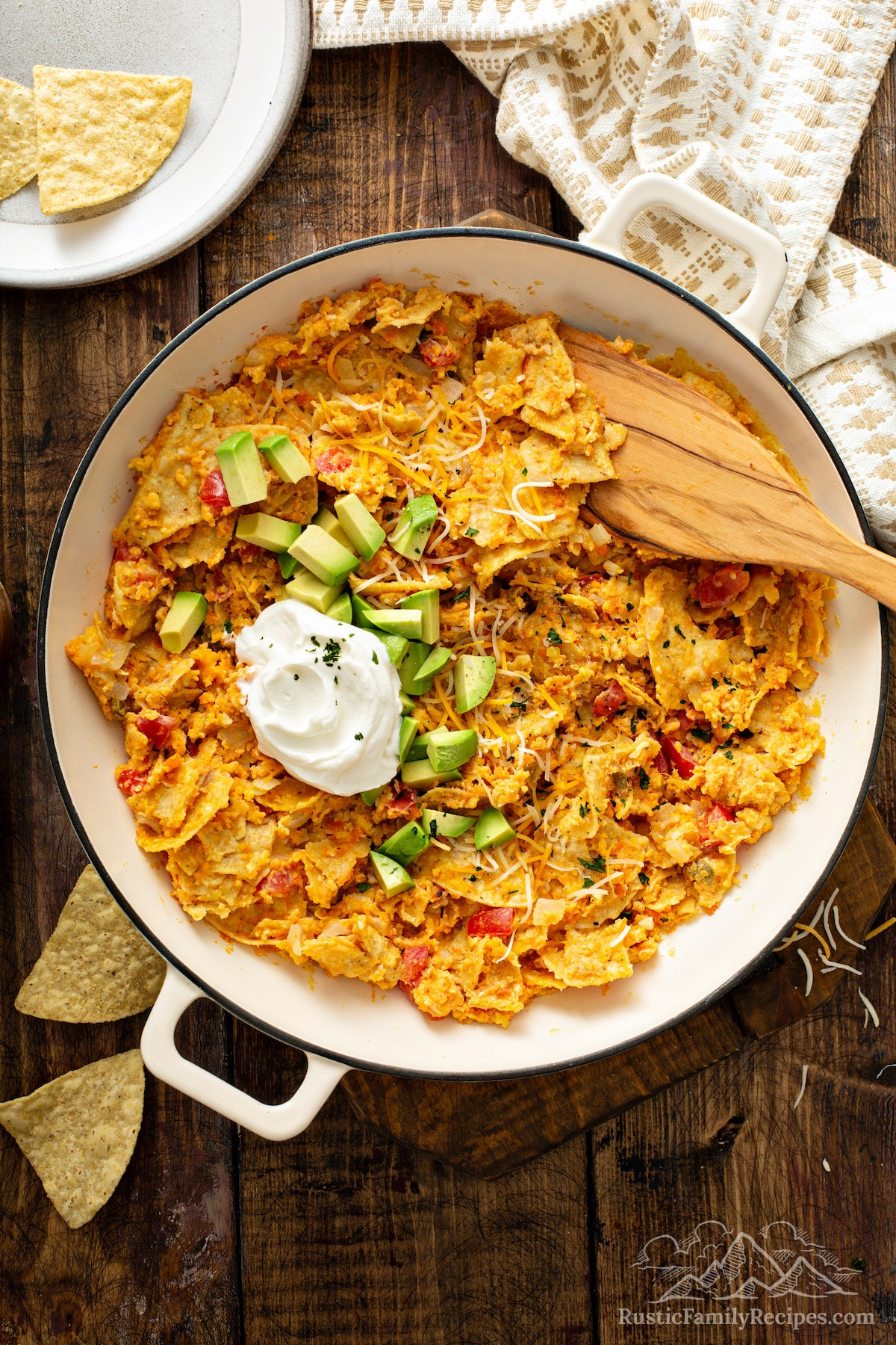 Sweet potato migas in a pan topped with avocado and sour cream