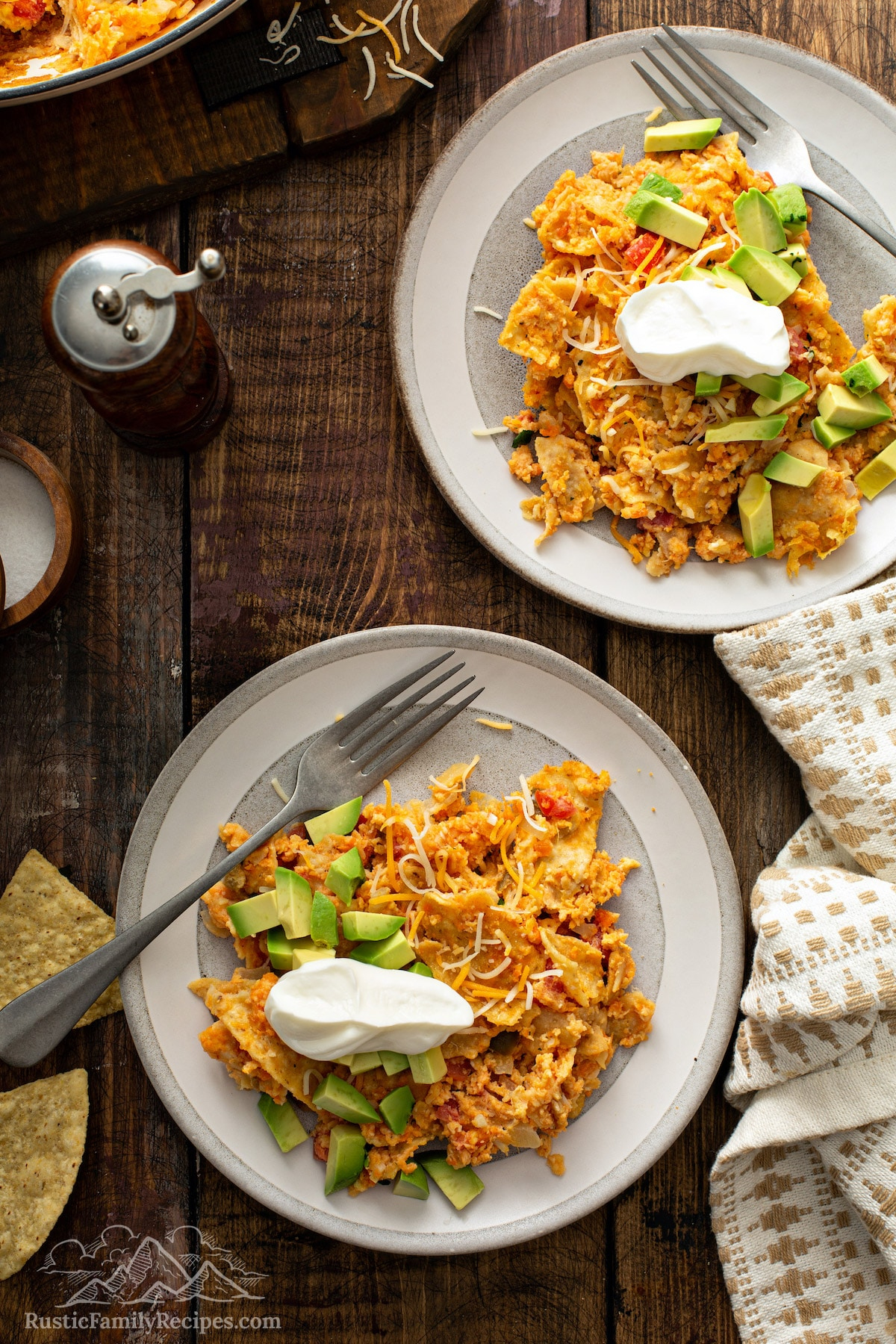 Two plates of migas with sweet potatoes, topped with sour cream and avocado