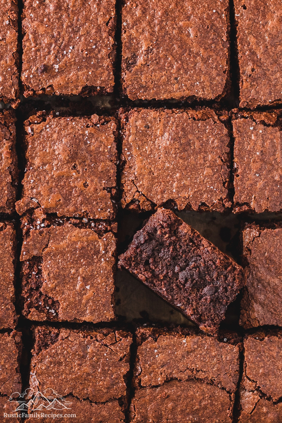 A close up of homemade brownie squares with one tilted so that you can see the chocolate center.