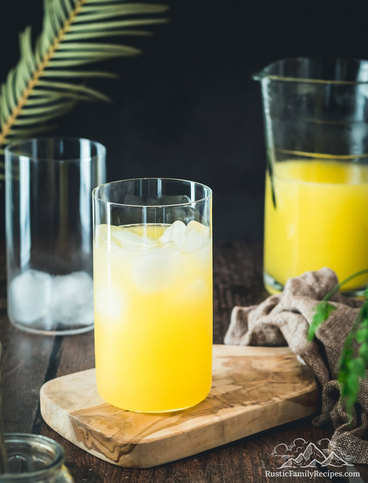 A glass of mango lemonade in front of a pitcher with lemonade