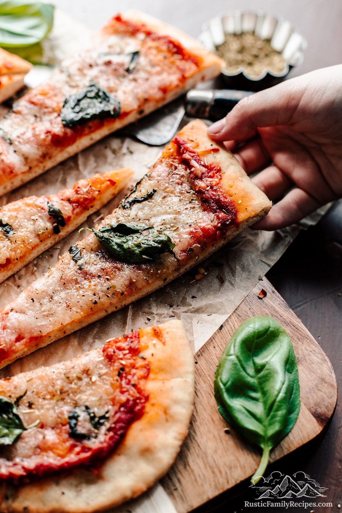 Slices of New York style sourdough pizza, a hand picking up a slice