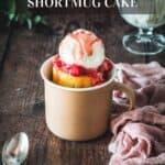 A pink mug on a wood table with vanilla mug cake, topped with ice cream