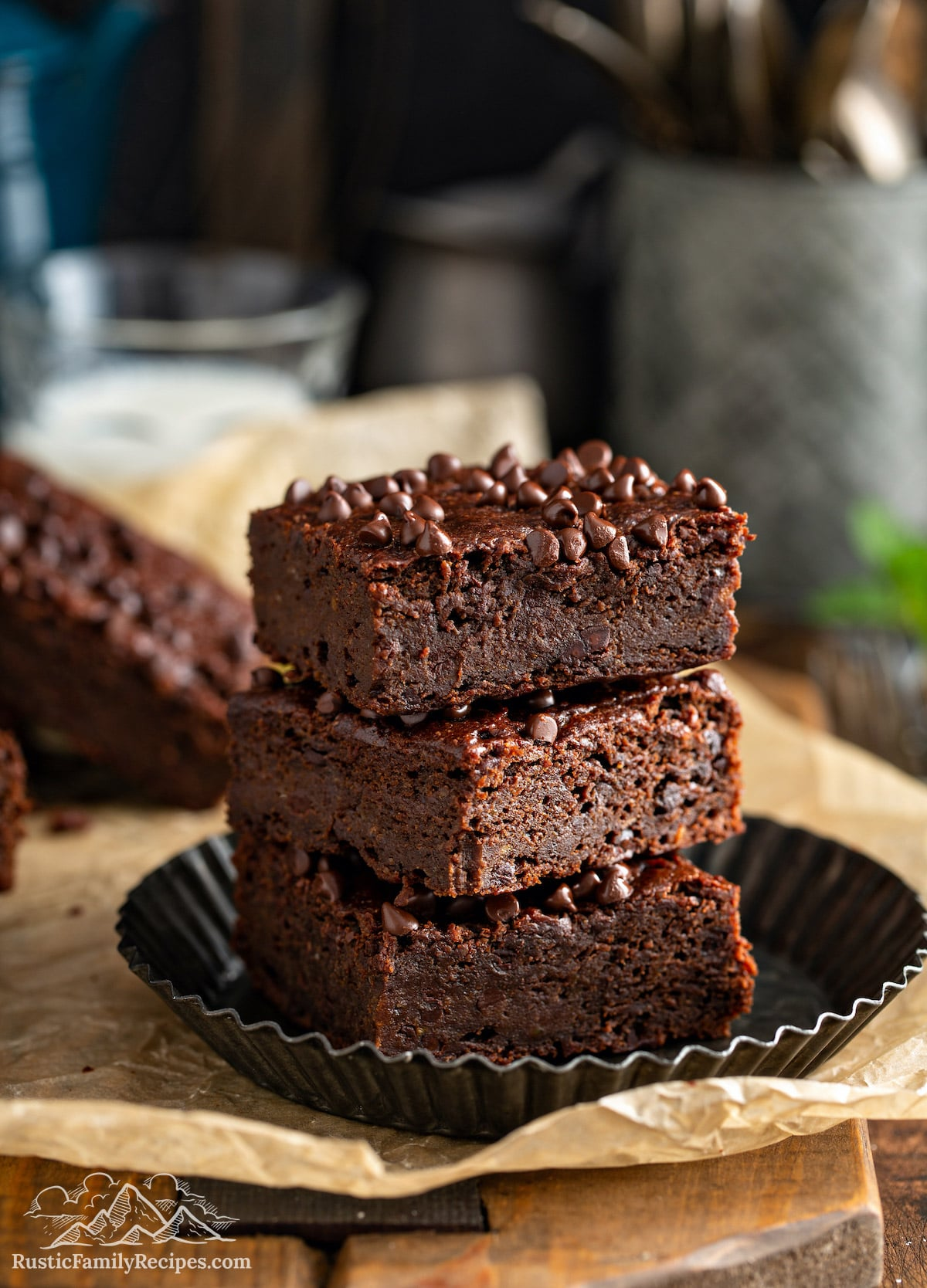 Three vegan brownies stacked on a plate