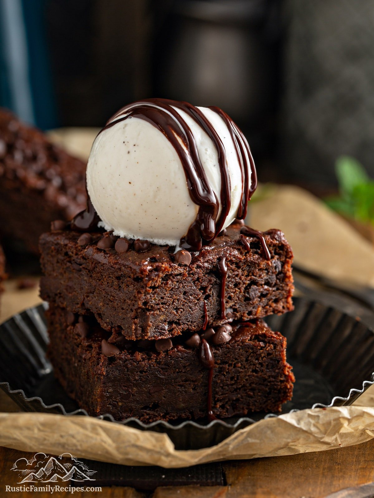 Two pumpkin sweet potato brownies stacked with vanilla ice cream on top