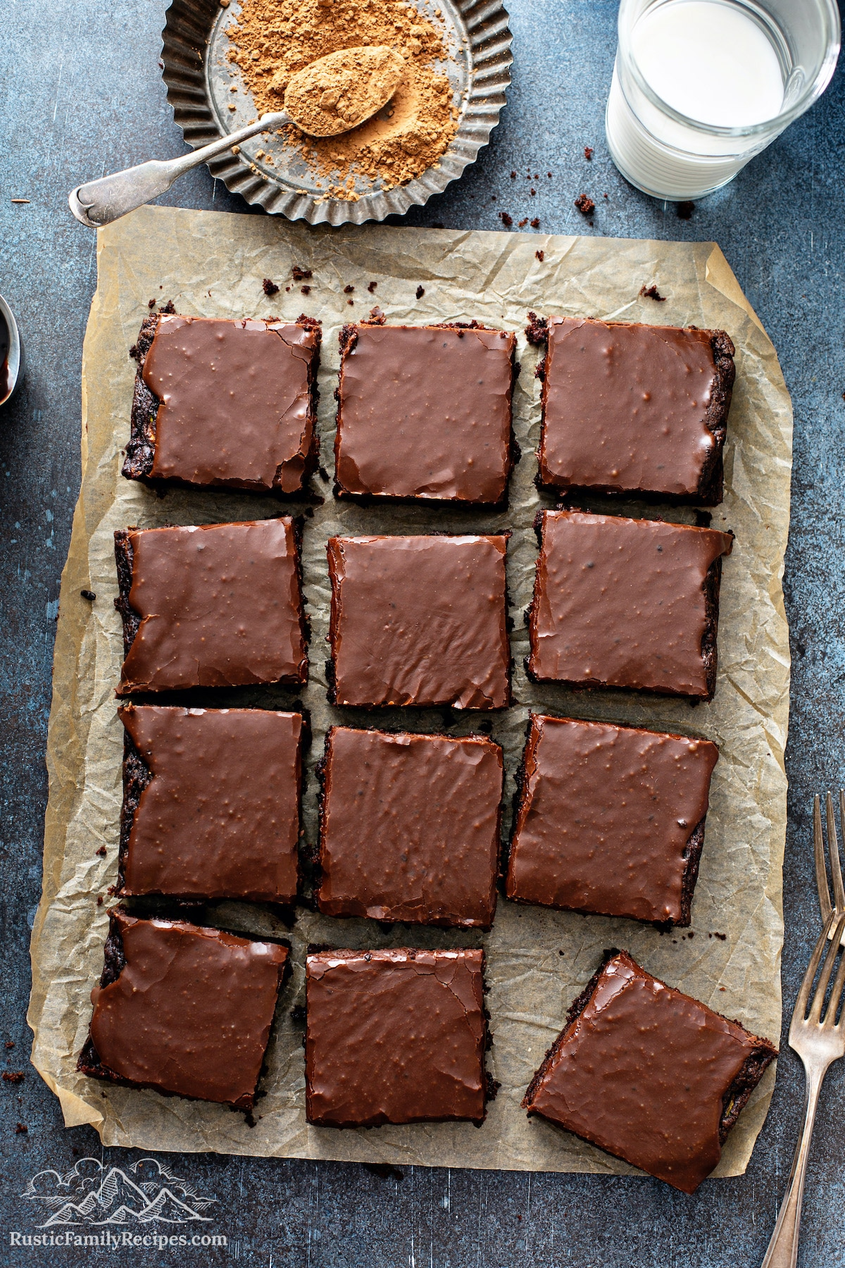 Frosted zucchini brownies on parchment paper with a glass of milk