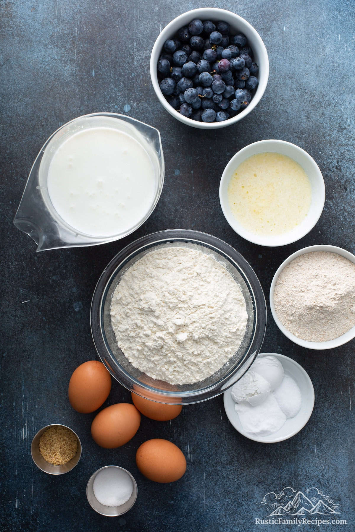 Everything you need for Blueberry Buttermilk Waffles: blueberries, sugar, all purpose and whole wheat flour, baking soda and powder, salt, wheat germ, four eggs, melted butter, and buttermilk.