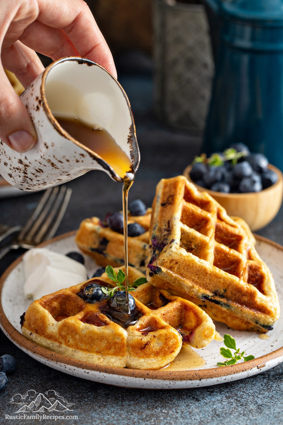 A plate full of fluffy Blueberry Buttermilk Waffles topped with blueberries and being drizzled with maple syrup.