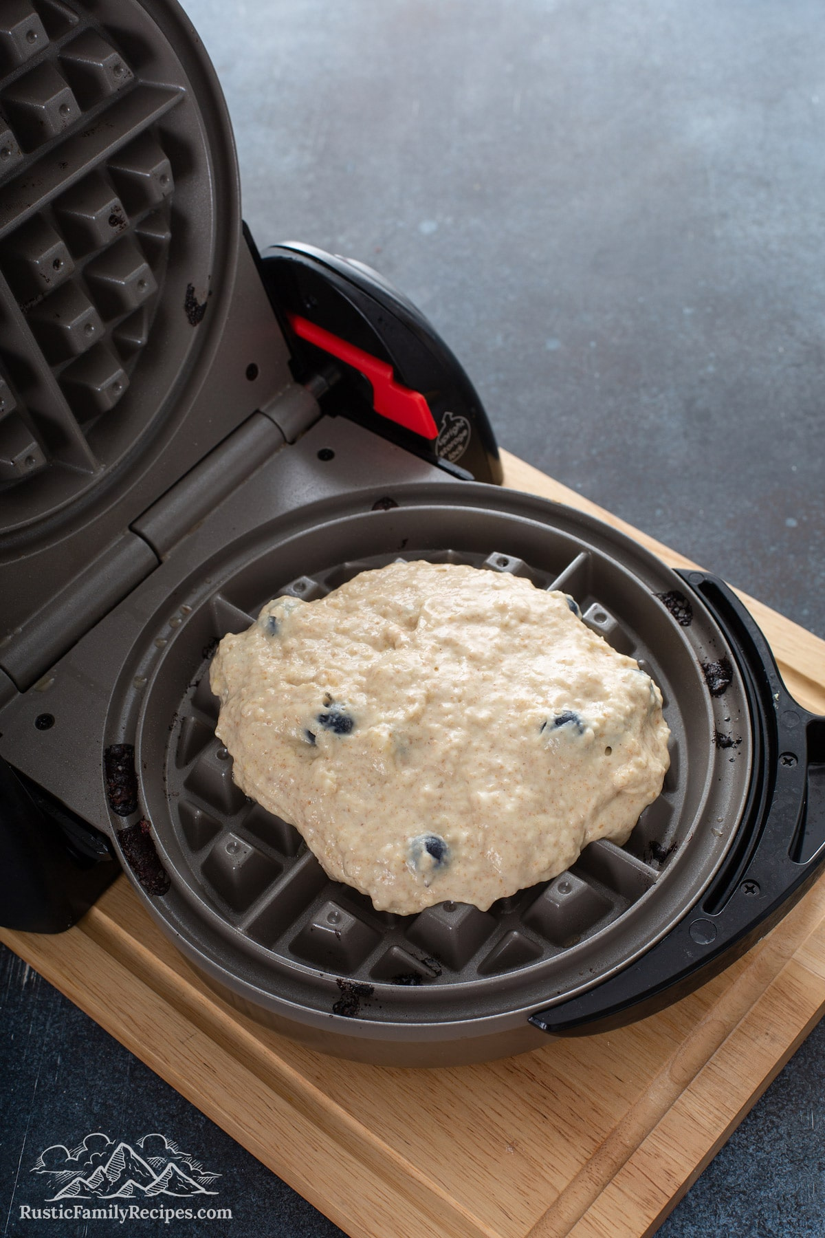 The batter spooned into the Belgian waffle maker.