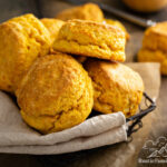 Sweet Potato Biscuits piled in basket, next to a cup of coffee