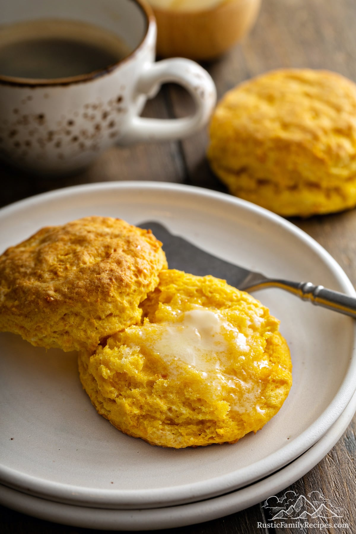 Halved Sweet Potato Biscuit topped with melted butter, on white plate