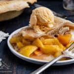 Slice of Peach Mango Pie on white plate, topped with scoop of vanilla ice cream
