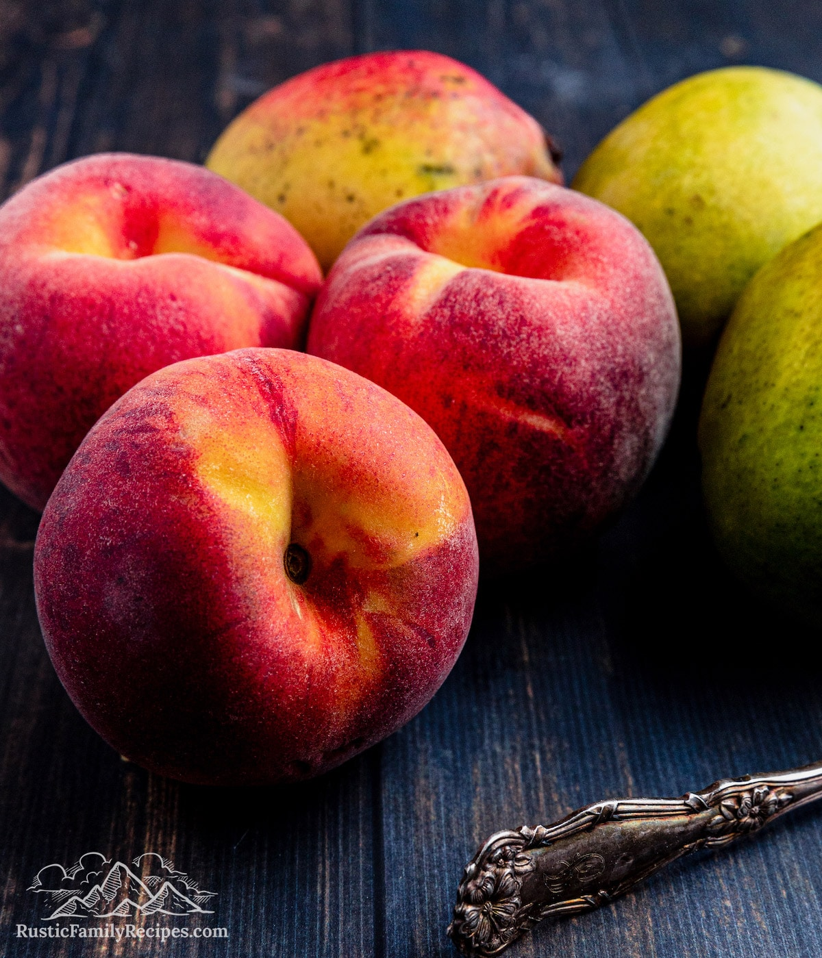 Closeup photo of 3 peaches, with 3 mangos in the background