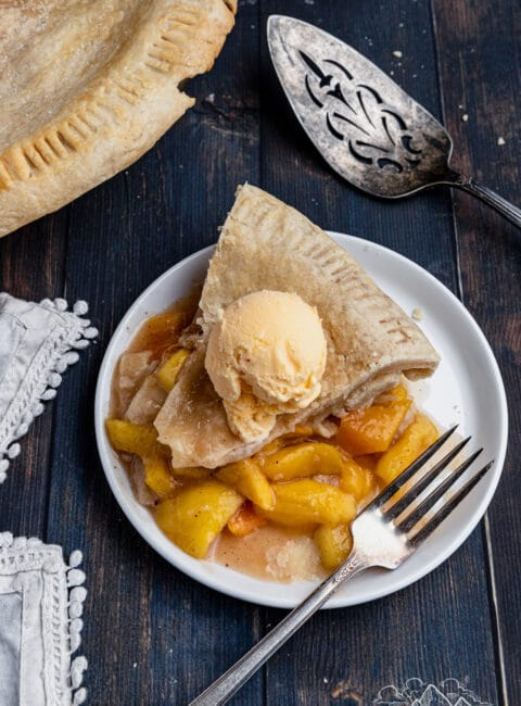 Overhead shot of Peach Mango Pie slice on white plate, topped with scoop of vanilla ice cream
